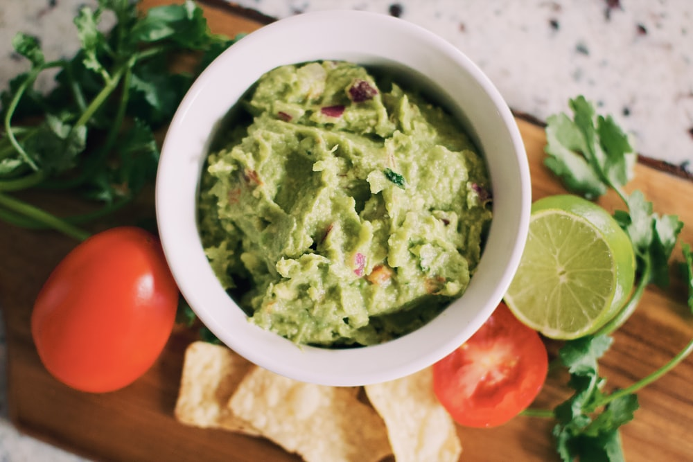 guacamole chip dip with carrots and lime unsplash